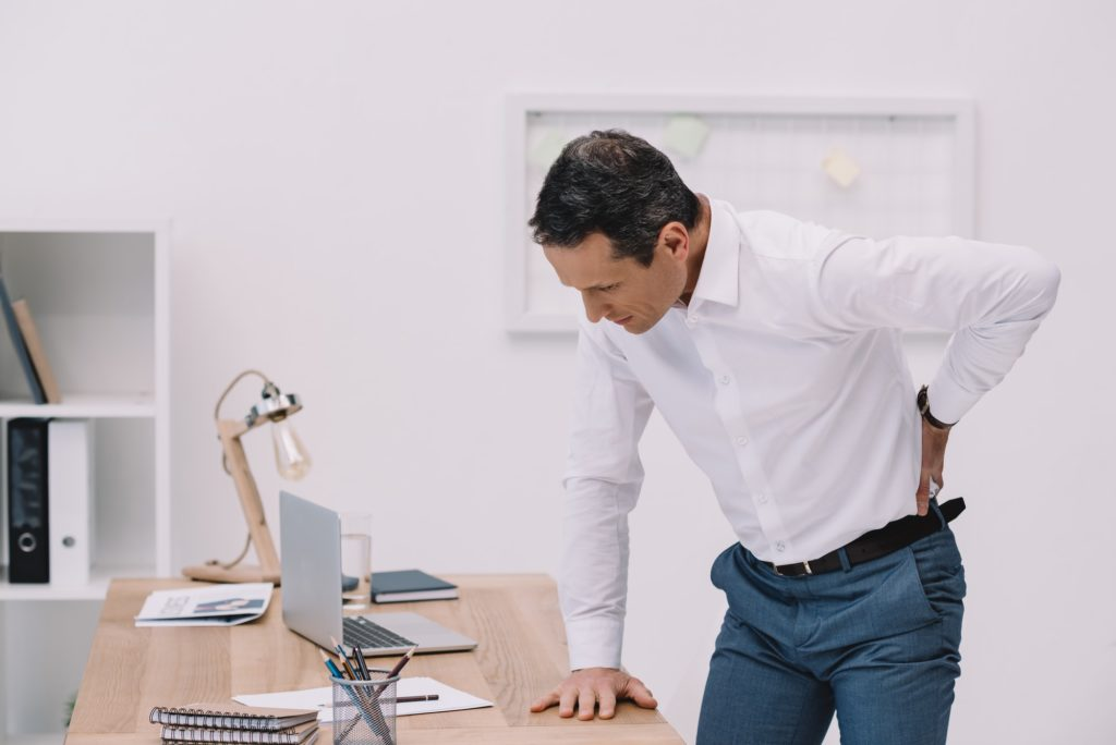 mature businessman with painful backache at office
